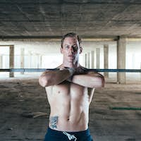 Man holding barbell with crossed arms