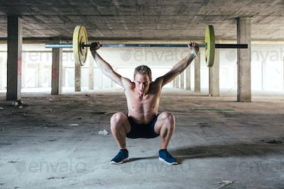 Man sitting and holding barbell overhead