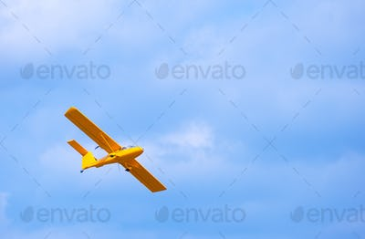 Yellow bright flying airplane in the blue sky