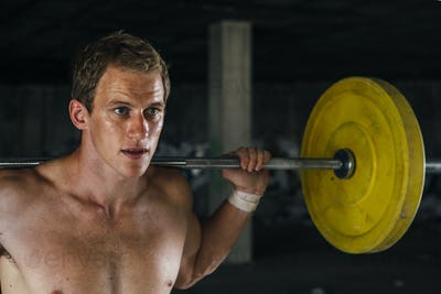 Man with naked torso lifting barbell