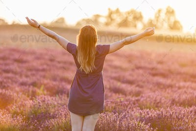 Happy young woman on lavender field at sunset