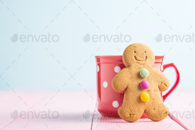 Gingerbread man leaning against a cup.