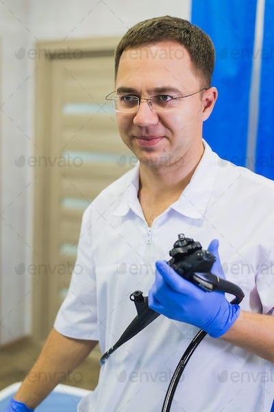 proctologist doctor holding Ligador hemorroidal in office