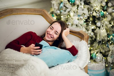 Young woman with mobile phone home lying on a sofa in front of fir tree