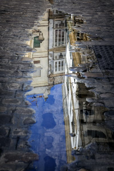 Buildings reflected in a puddle in the street
