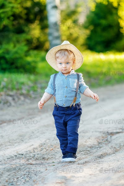 Toddler child outdoors. Rural scene with one year old baby boy wearing straw hat