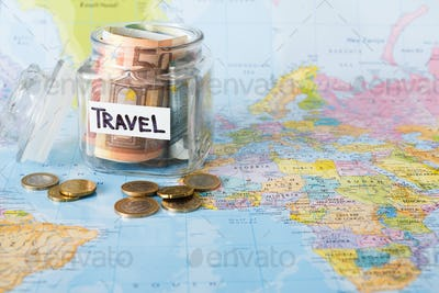 Travel budget concept. Money saved for vacation in glass jar on map background
