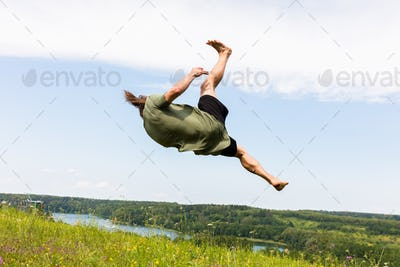 Young man jumping on a hill.