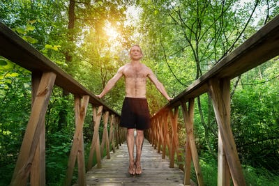 Young man standing on a footbridge in the forest.