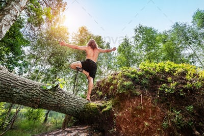 Young man standing on a tree trunk in the forest.