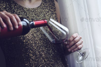 woman with gold spangle dress pouring red wine into a glass