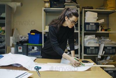 woman fashion designer at work in authentic workshop interior
