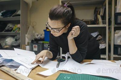 female fashion designer at work in authentic workshop interior