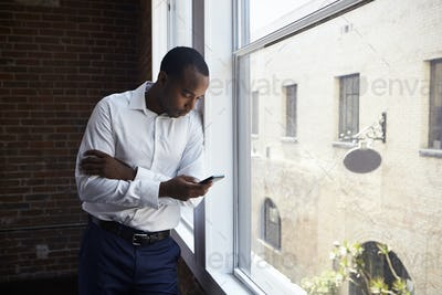 Businessman Checking Phone Standing By Office Window