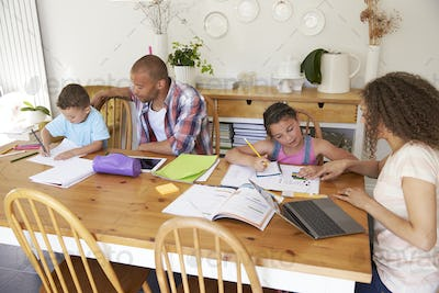 Parents Helping Children With Homework At Table