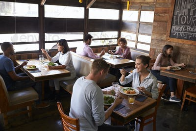 Couples relaxing over lunch in a restaurant, elevated view
