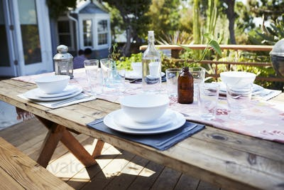 Table Set For Outdoor Meal On Wooden Table In Garden
