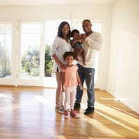 Portrait Of Family In New Home On Moving Day