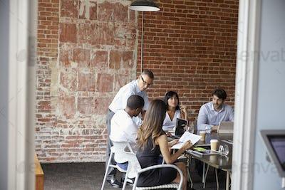 Businesspeople Meeting In Modern Boardroom Through Doorway