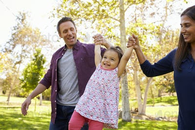 Mixed race couple lifting young daughter in park, close up