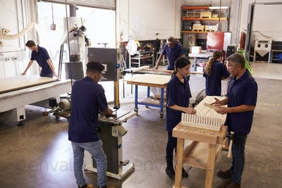 Carpenters Working On Machines In Busy Woodworking Workshop