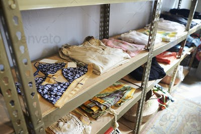 Clothing displayed on shelves in clothes shop, elevated view