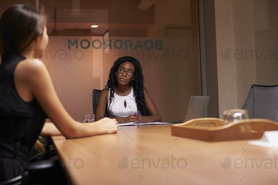 Two corporate businesswomen at an evening meeting in office