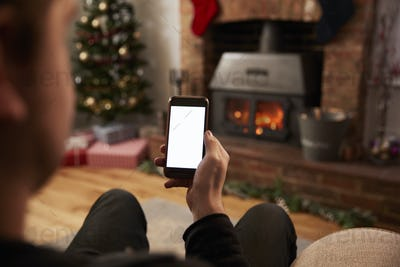Man Using Mobile Phone In Room Decorated For Christmas