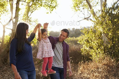Mixed race couple walk on rural path lifting young daughter