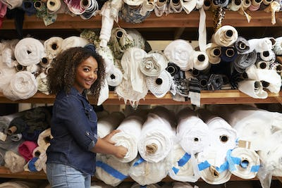 Mixed race woman selecting fabrics looking to camera