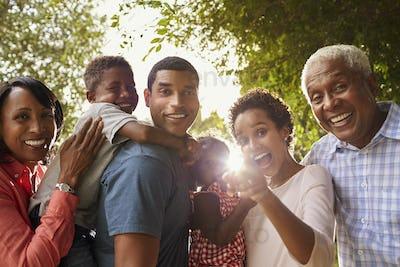 Multi generation black family in garden look to camera