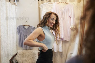 Woman trying on a skirt in a boutique changing room