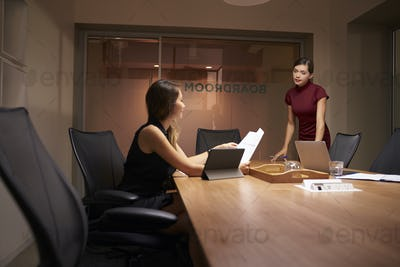 Businesswoman stands talking to colleague working late