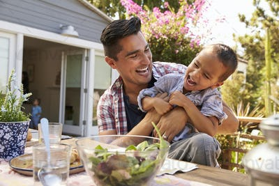 Father And Son Eating Outdoor Meal In Garden Together