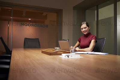 Young businesswoman working late in office smiles to camera