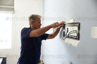 Man Fitting Bracket For Flat Screen TV Onto Wall
