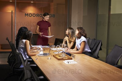 Female boss and colleagues at an evening business meeting