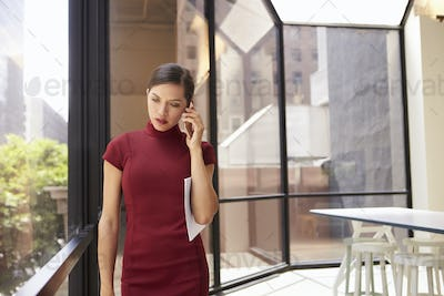 Young young white businesswoman using phone in modern office