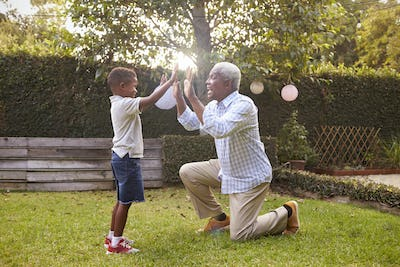 Black grandfather plays with grandson in garden, full length