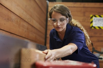 Female Carpenter Using Plane In Woodworking Woodshop