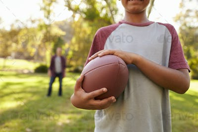 Boy holding football in park, crop, dad in background