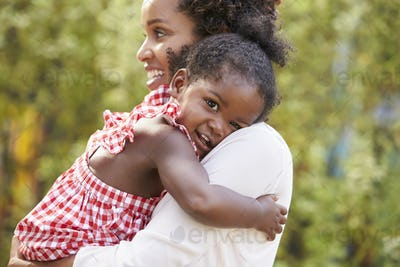 African American mother embracing with baby daughter