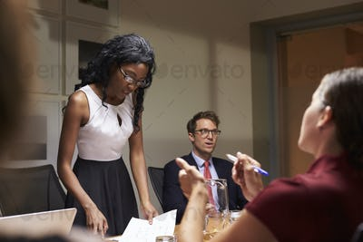 Black businesswoman reading to team at meeting, low angle