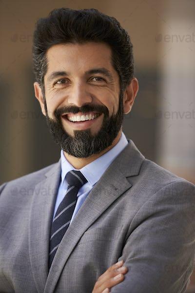 Middle aged Hispanic businessman smiling to camera, close up