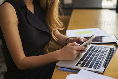 Businesswoman using smartphone in office, mid section, side view