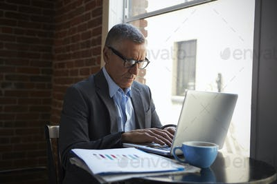 Mature Businessman Working On Laptop By Office Window