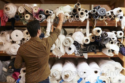 Man reaching to select fabric from storage shelves