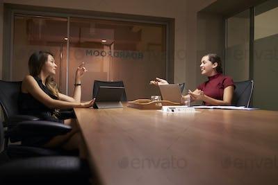 Two businesswomen working late in an office talking