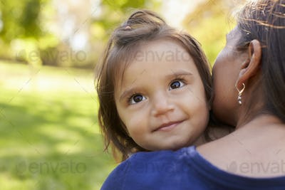 Mixed race mother holding her daughter, over shoulder view