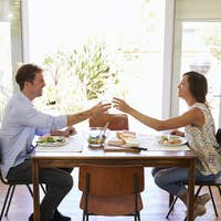 Couple Make A Toast As They Enjoy Meal At Home Together